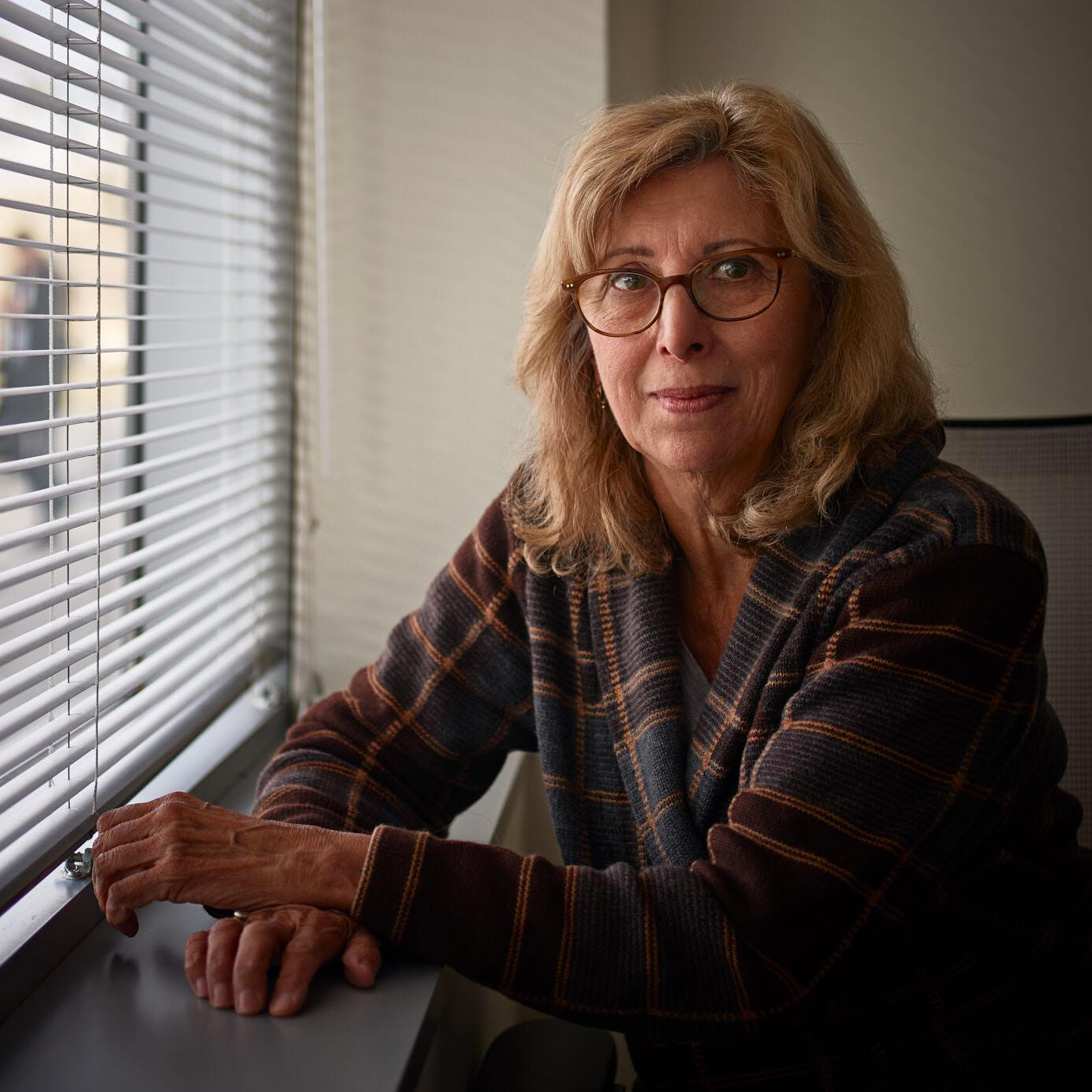 Michelle Smith sits next to a window with blinds on it with her hands crossed on the window sill. She has shoulder length blond hair and is wearing red rimmed glasses, she is also wearing a plaid jacket.