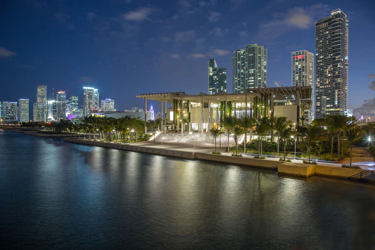 Photo of a contemporary building (the Perez Art Museum Miami) from the water. It's dusk and the Miami skyline is visible in the background.