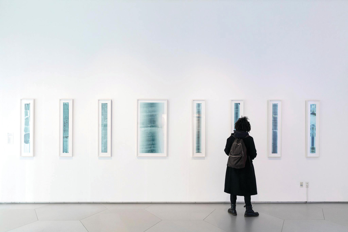 A woman looks at a wall with several pictures in blue.