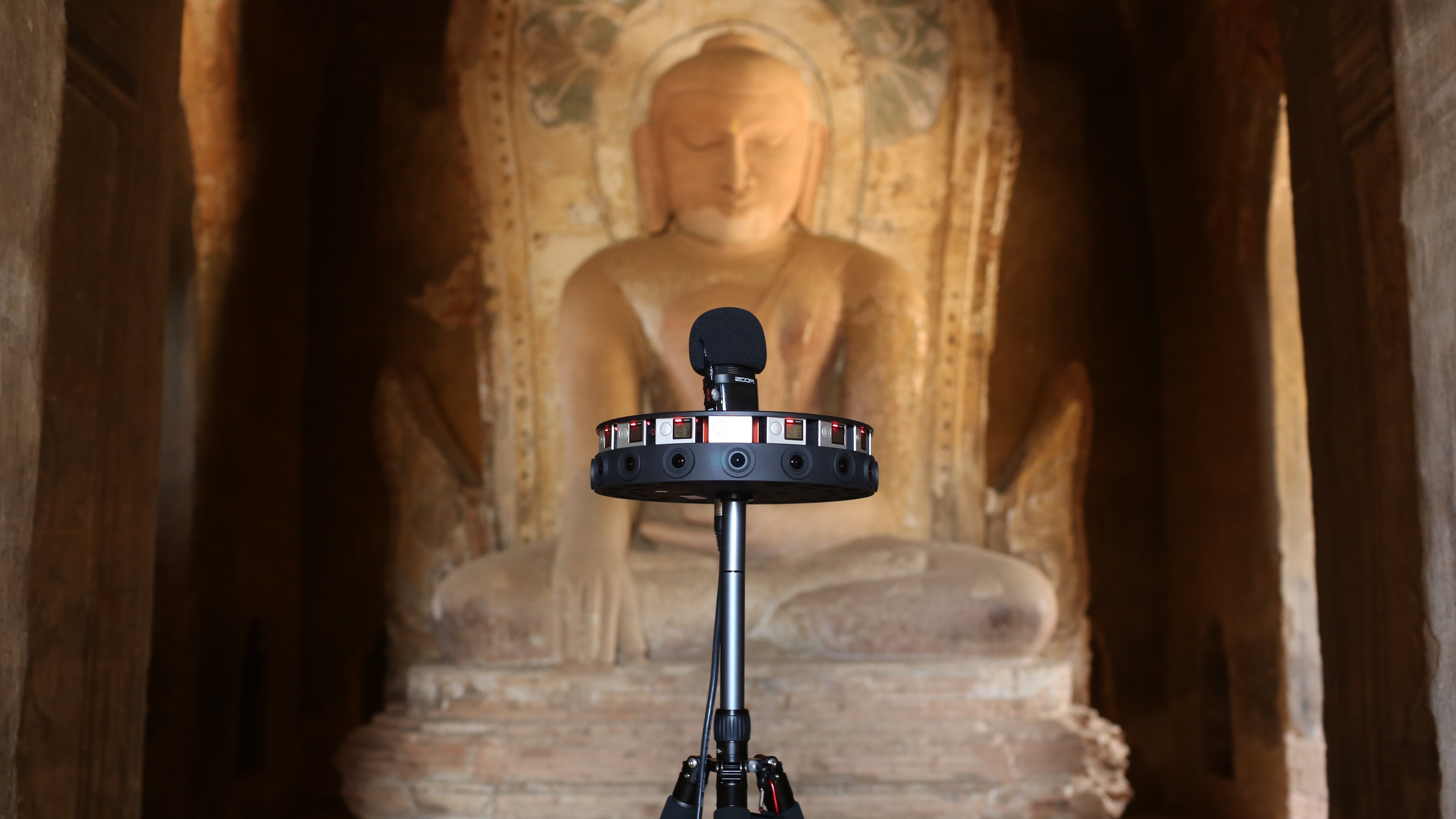 A microphone with a wheel attached sits in front of a Buddha statue