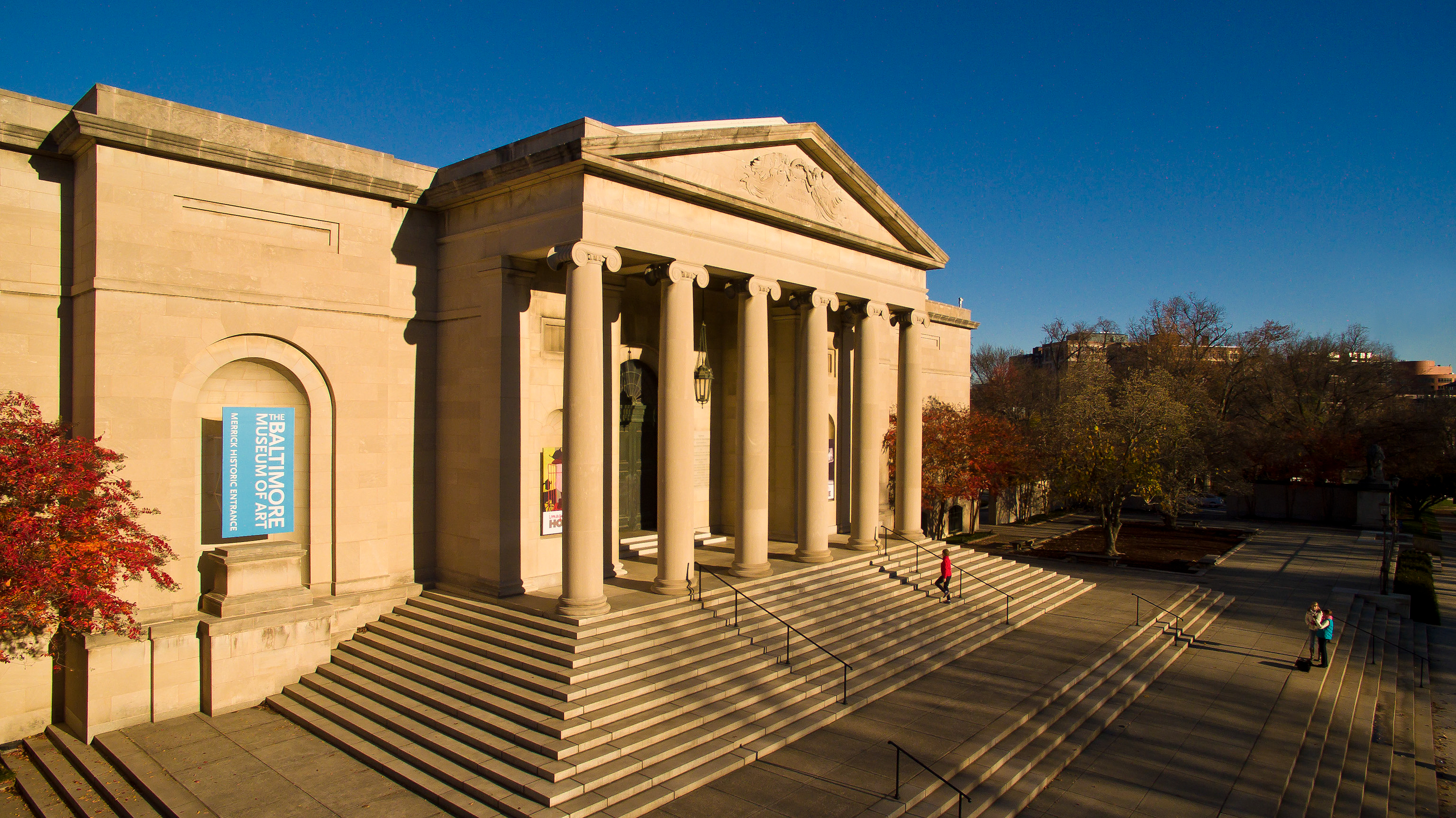 Exterior of a classical style building with ionic columns and two sets of stairs.
