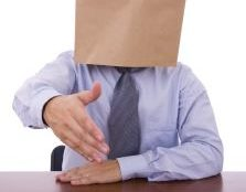 A man with a paper bag over his head extends his hand to greet to the viewer, As if he is entering an interview.