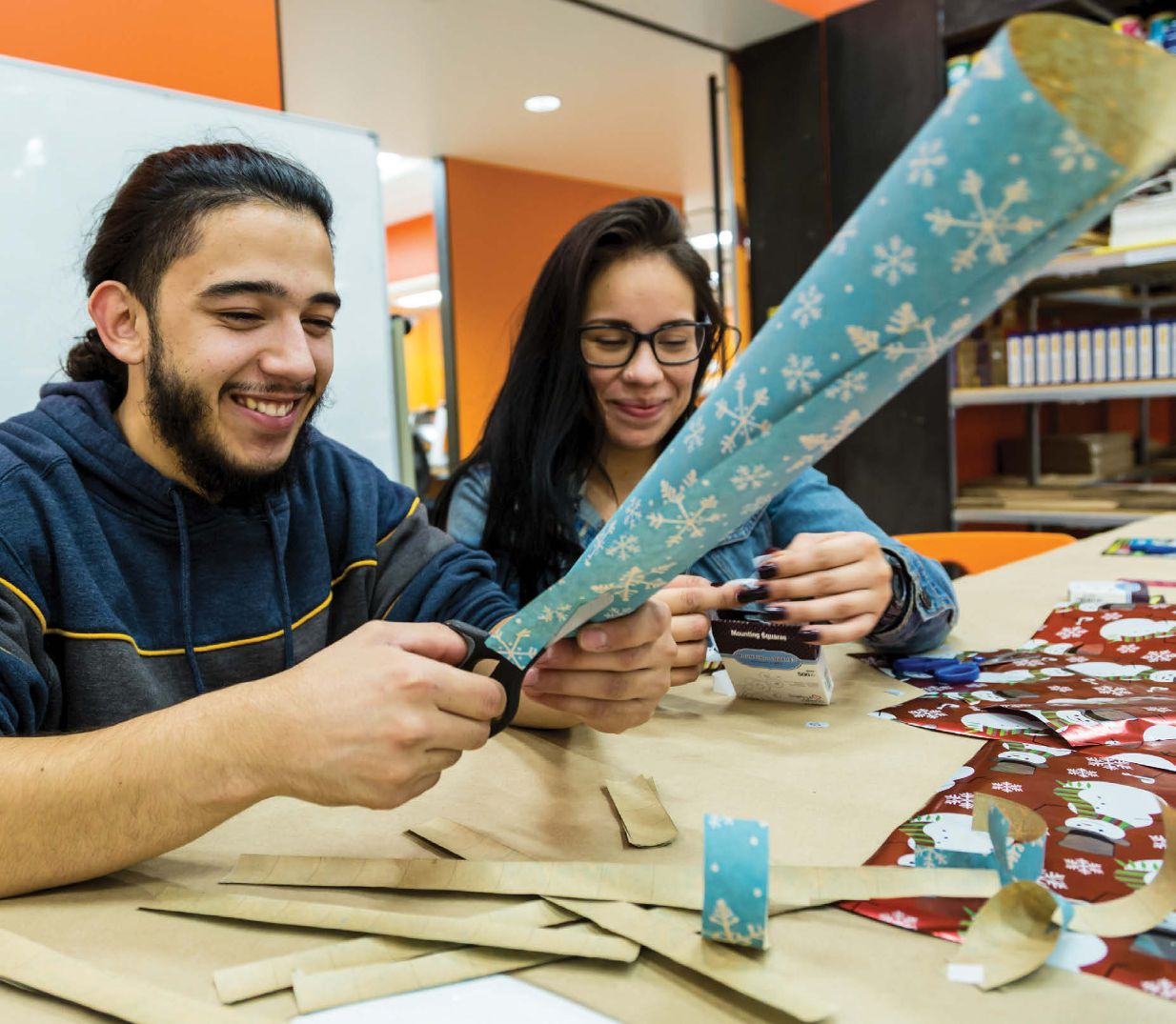 A young hispanic man and a young hispanic woman sit at a table with various wrapping paper smiling and making various crafts.
