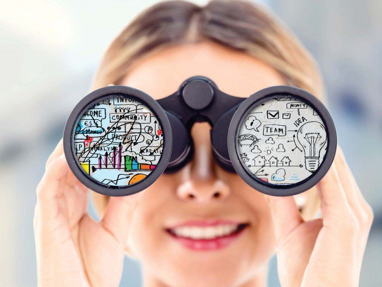 A woman looking through binoculars with various teambuilding terms on the glass.