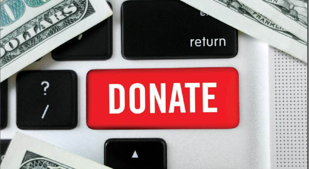 Closeup image of a keyboard with a red Donate button and cash laid over it.