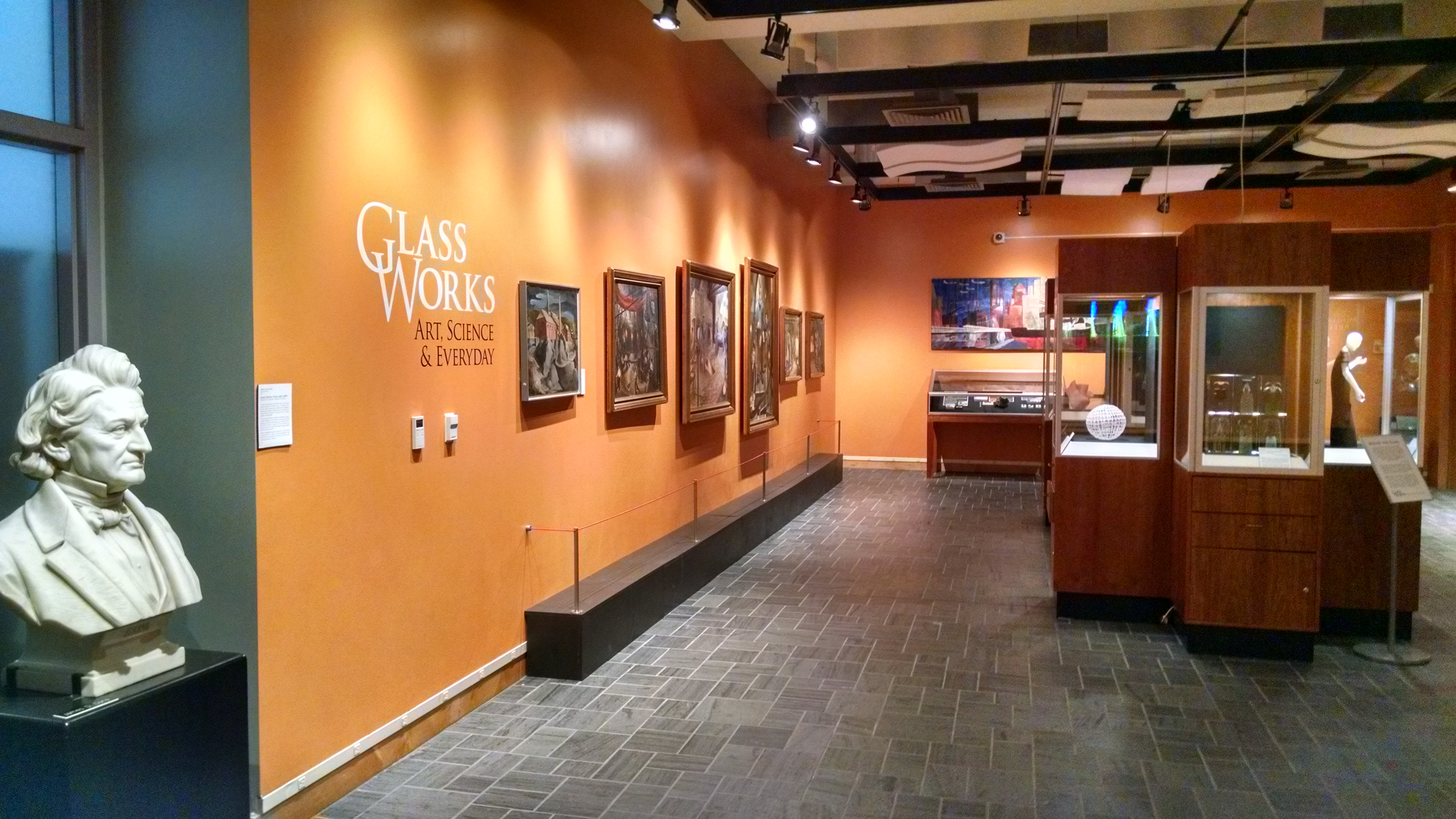 "A picture of an exhibit of paintings in a gallery space with orange walls with the label ""Glass Works"" on the wall and a series of paintings featuring"