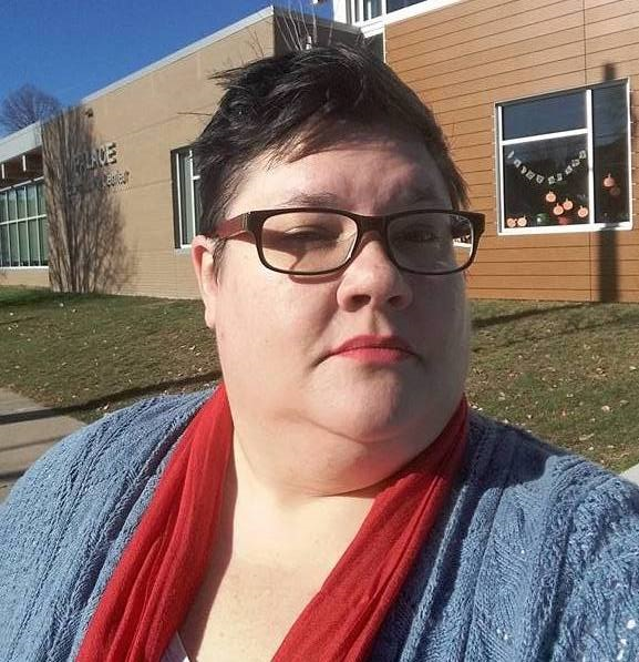 Selfie shot of a woman with close cropped dark hair standing outside a building wearing square shaped dark rimmed classes, a light blue v-neck sweater with a white tank top and orange scarf.