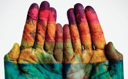 Image of two open hands facing the camera with various colors painted all over them.
