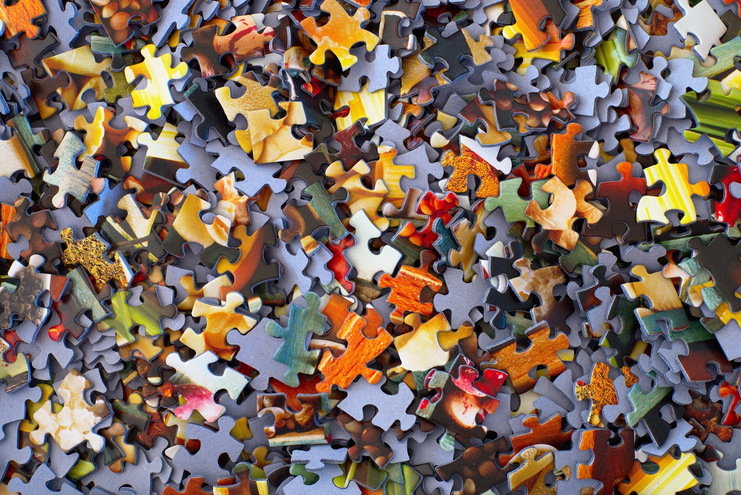 Closeup image of hundreds of puzzle pieces thrown on top of one another some right side up some upside down.