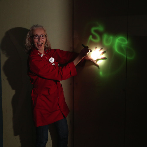 A woman stands next to a light shining on a wall with green letters spelling out Sue. She looks extremely excited with her mouth open, wearing a red lab coat.