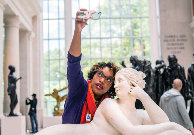 A black woman stands behind a Grecian statue taking a selfie.