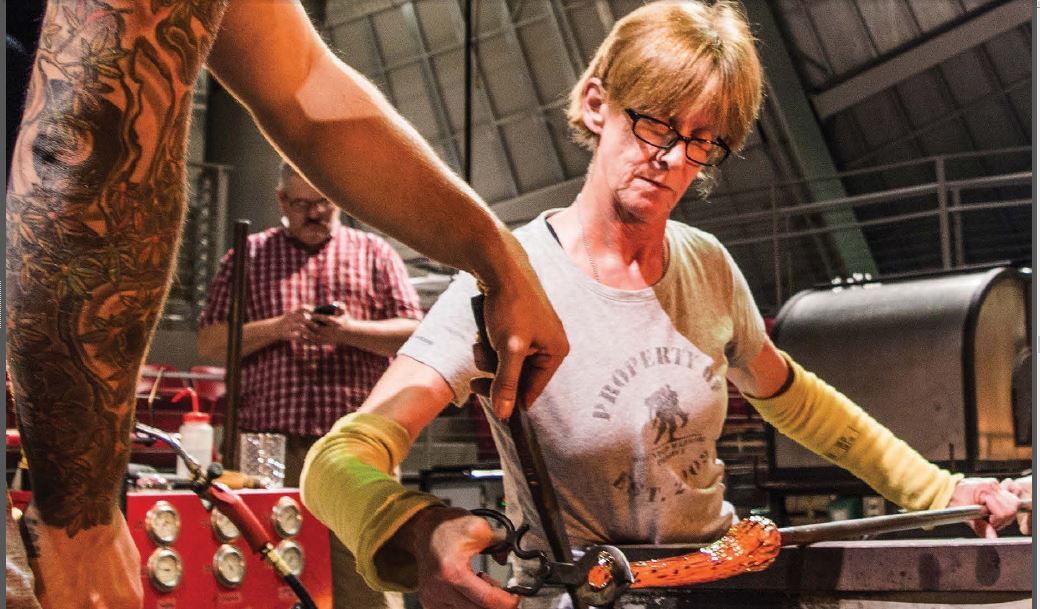 A woman works a piece of glass on a metal tube.