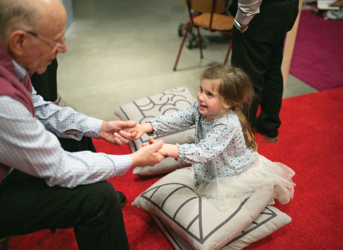 A little girl in a patterned shirt and tutu skirt kneels on a set of pillows facing an older gentleman who is clasping her hands and smiling.