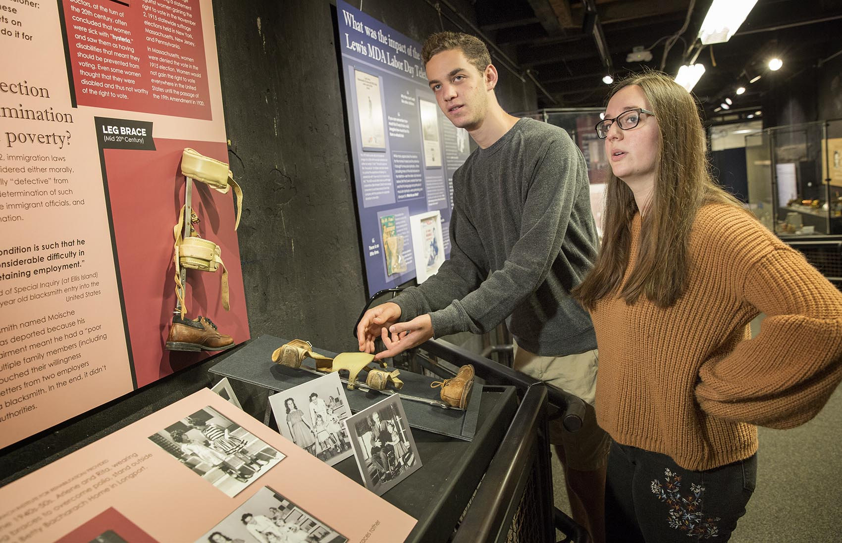 Two students stand at a display case in their exhibit.
