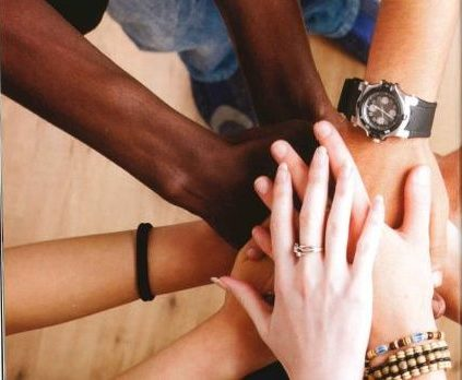 View of a group of different skin tone hands one on top of the other.