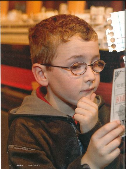 "A young visitor to""Titanic: The Artifact Exhibition"" studies the boarding pass of an actual passenger on the ill-fated ship."