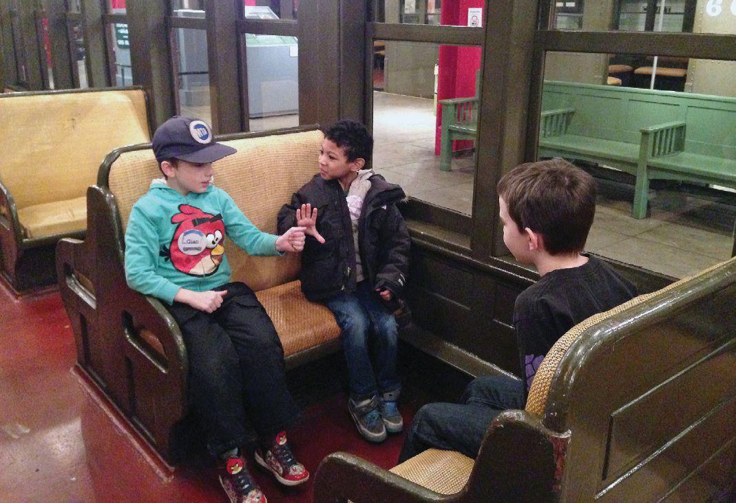 Three boys sit in a train car exhibited in a gallery.