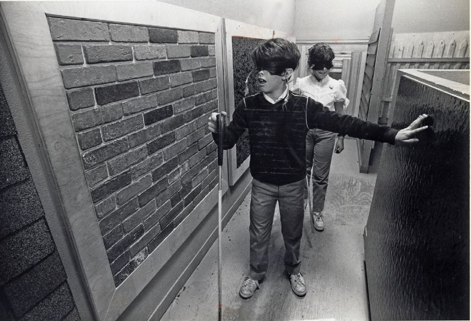 Two young men walk down a hallway with various wall treatments (for example brick, concrete) wearing blindfolds and carrying walking canes that a person with blindness might use.