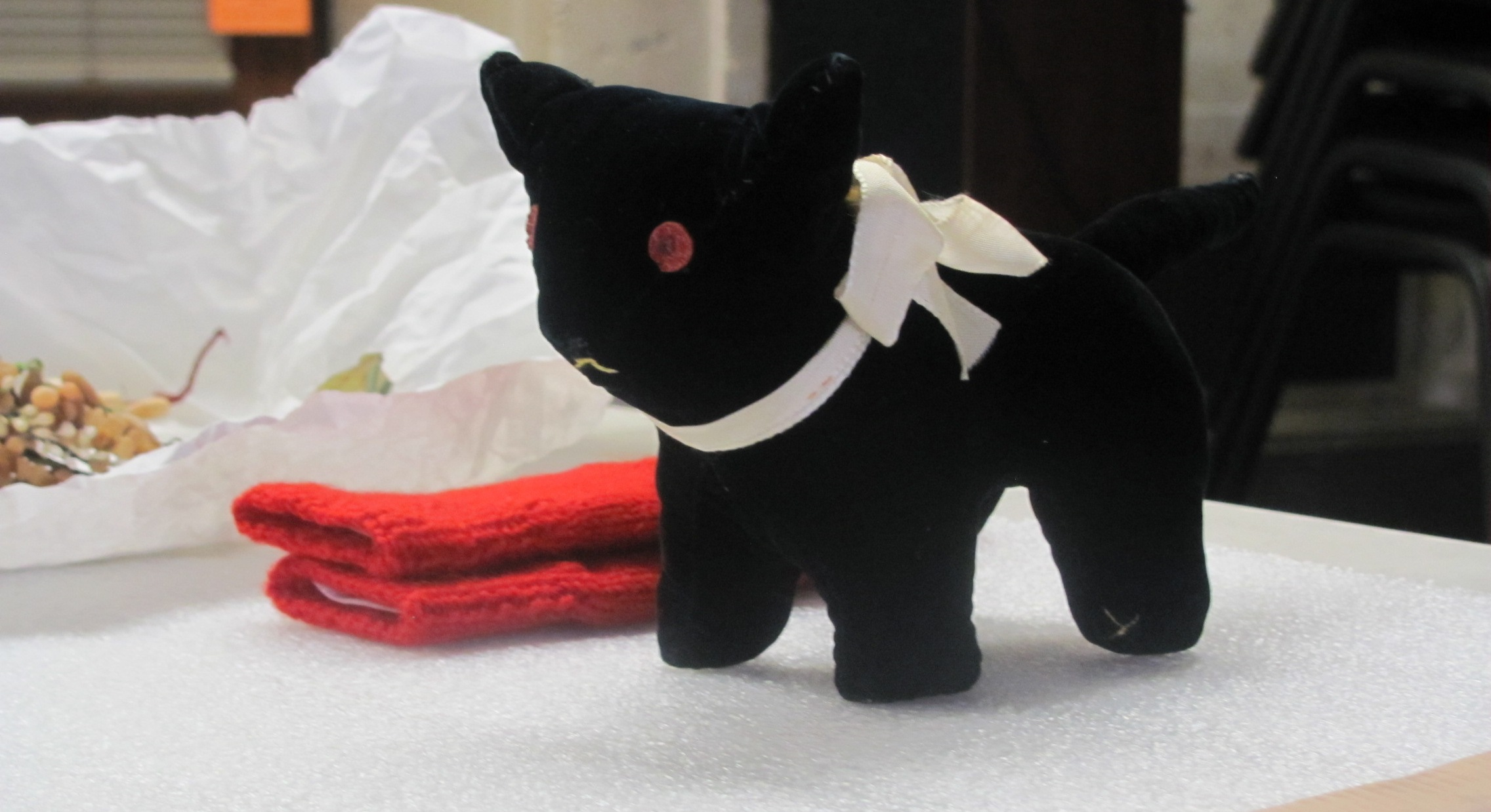 A small black stuffed animal cat sits on a table with various other collections items behind it.