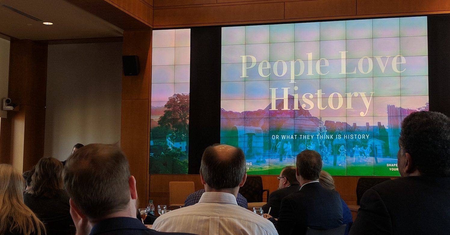 """View of the conference room where the historic house summit was held with a group of mainly men looking at a screen with """"People Love History"""" displayed on it."""