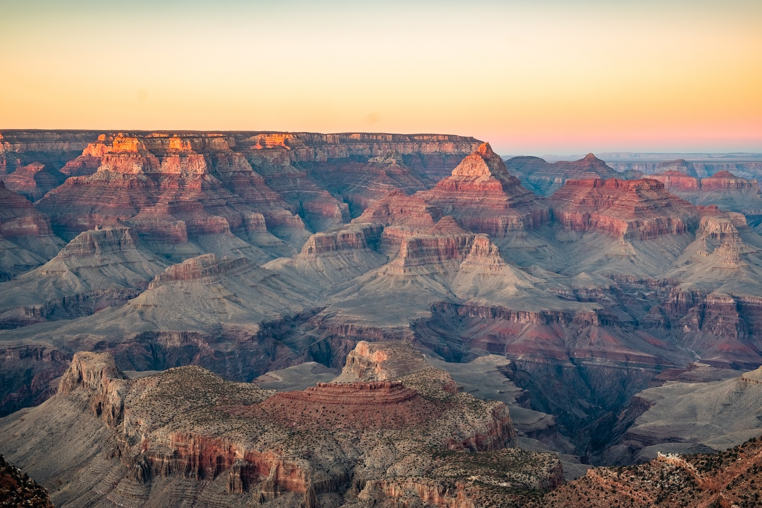 Wide image of the Grand Canyon with lots of oranges and reds.