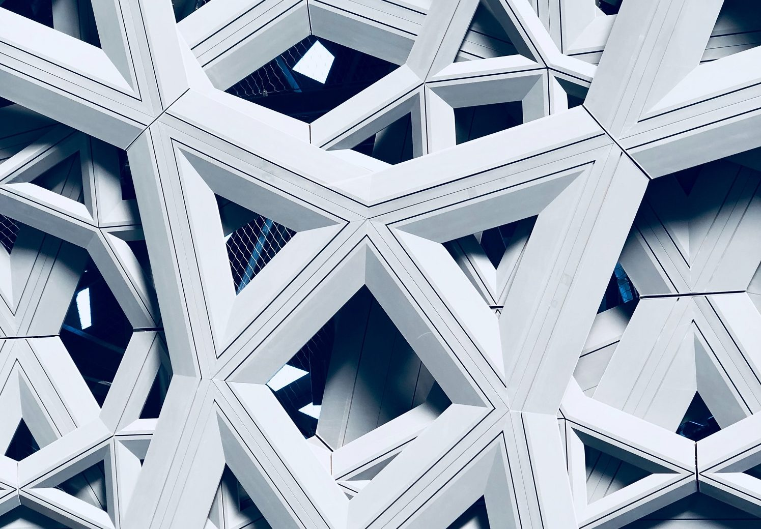 View of a portion of the Louvre Abu Dhabi with intricate interwoven structures and windows framed within.
