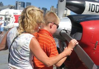A boy who is blind touches the T-34 Mentor during a touch tour for families.