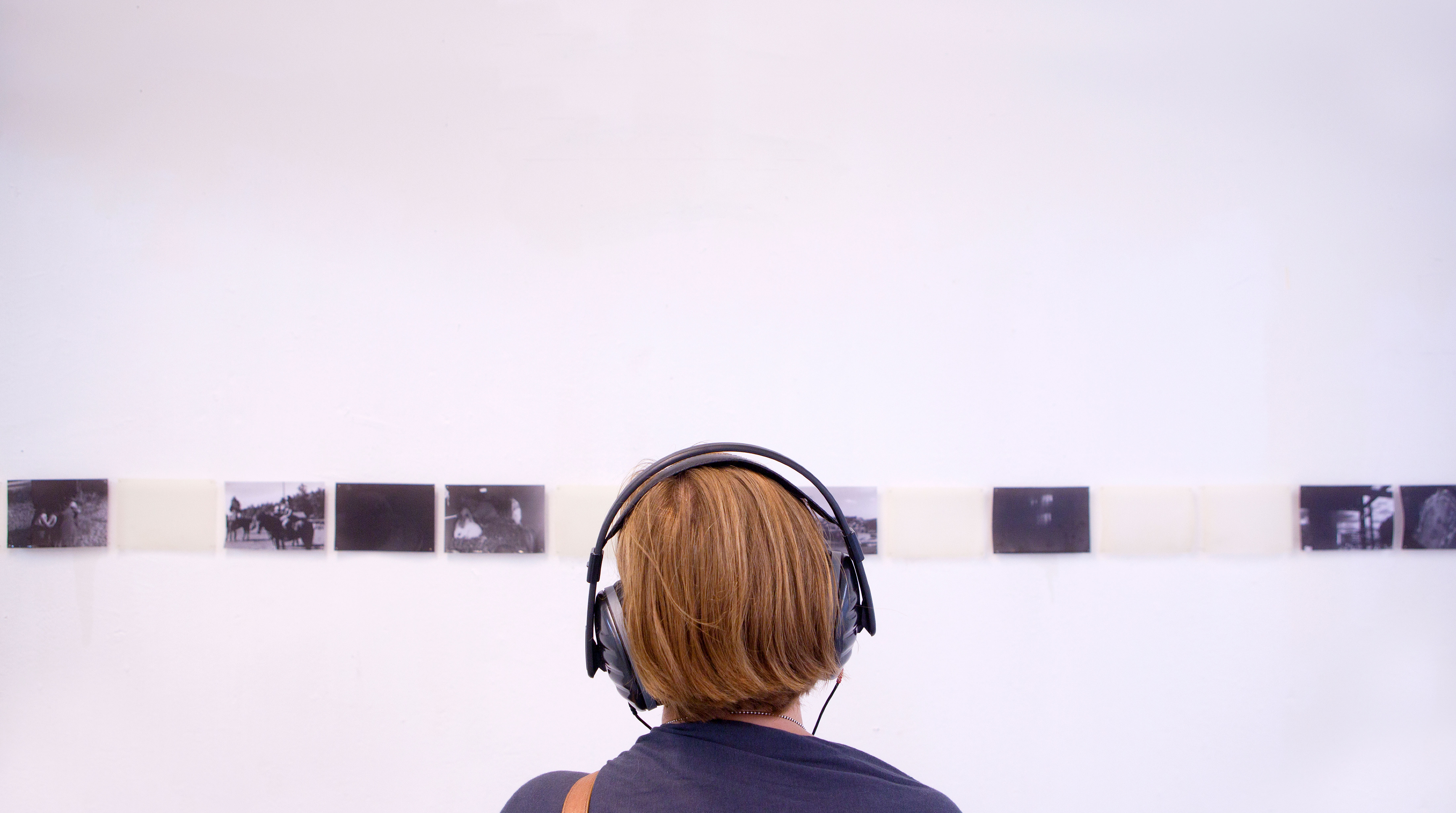Person wearing headphones looking at photography exhibition.