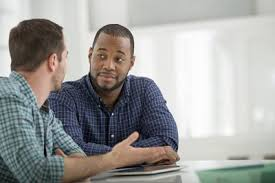 A white man and a black man sit at a table discussing something important.