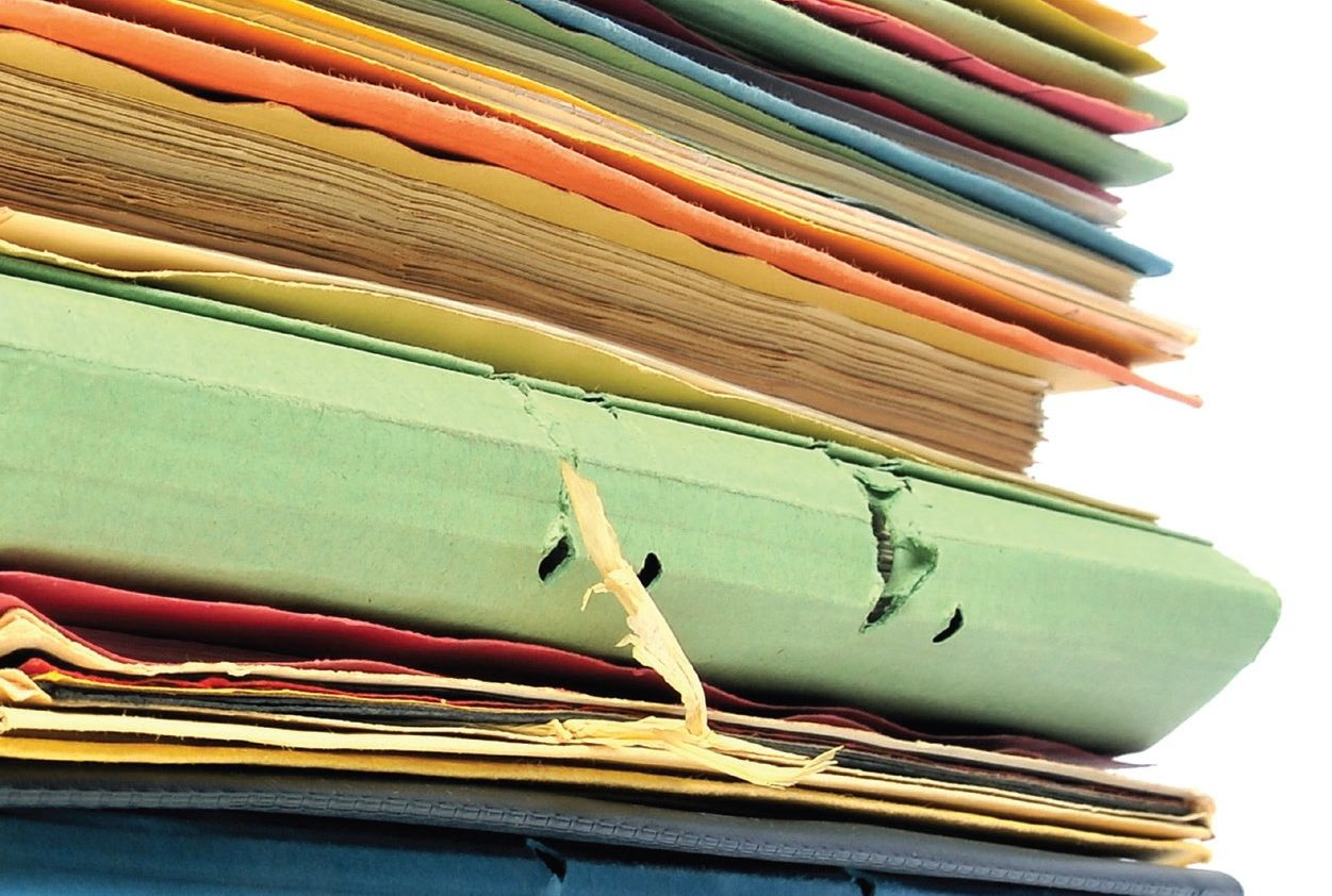 View of a stack of pagers and folders in varying colors.