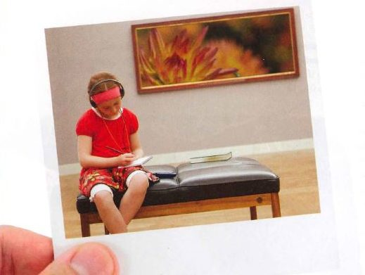 Image of a person's hand holding a Poloroid image of a girl sitting on a bench in a gallery.