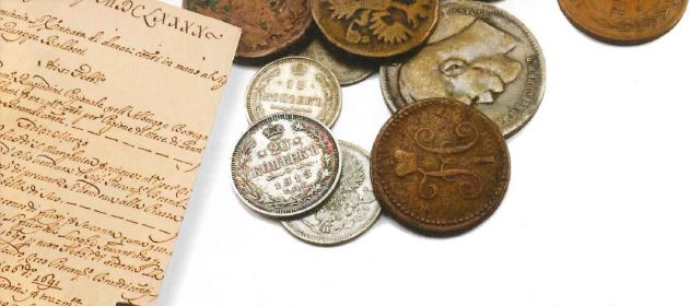 A historical document and a series of coins stacked on top of each other.