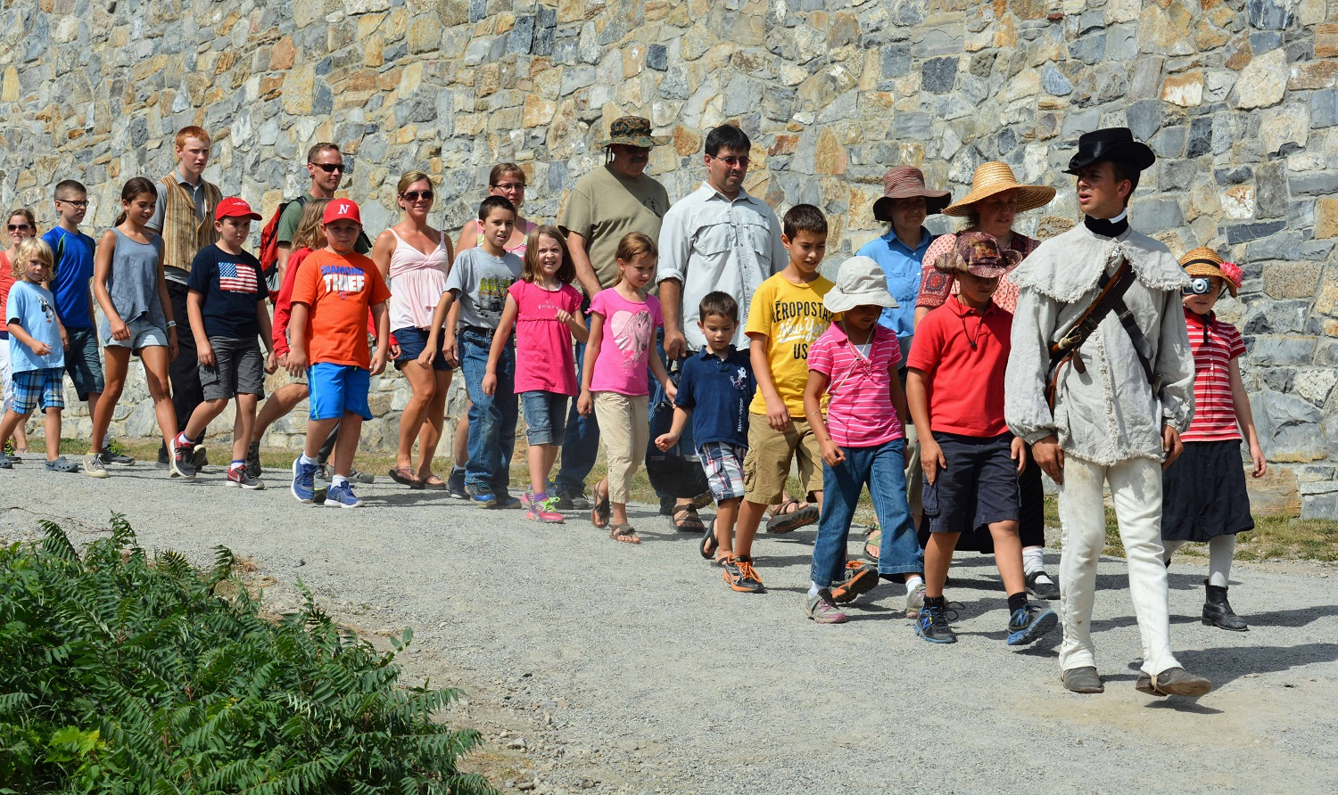 A double line of children and adults walking next to a stone wall.