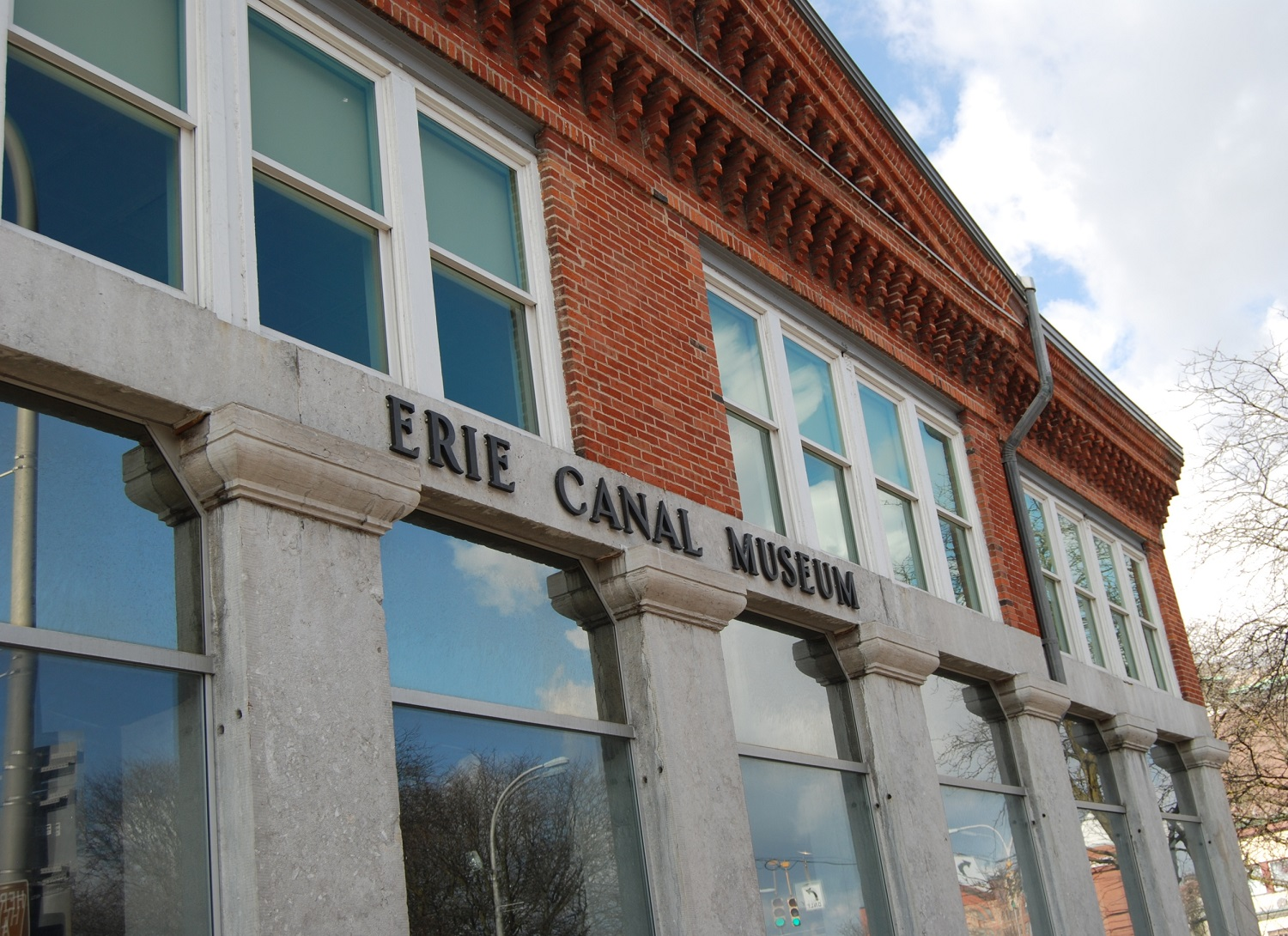 Exterior shot of a red brick and concrete building with Erie Canal Museum in writing on the front.
