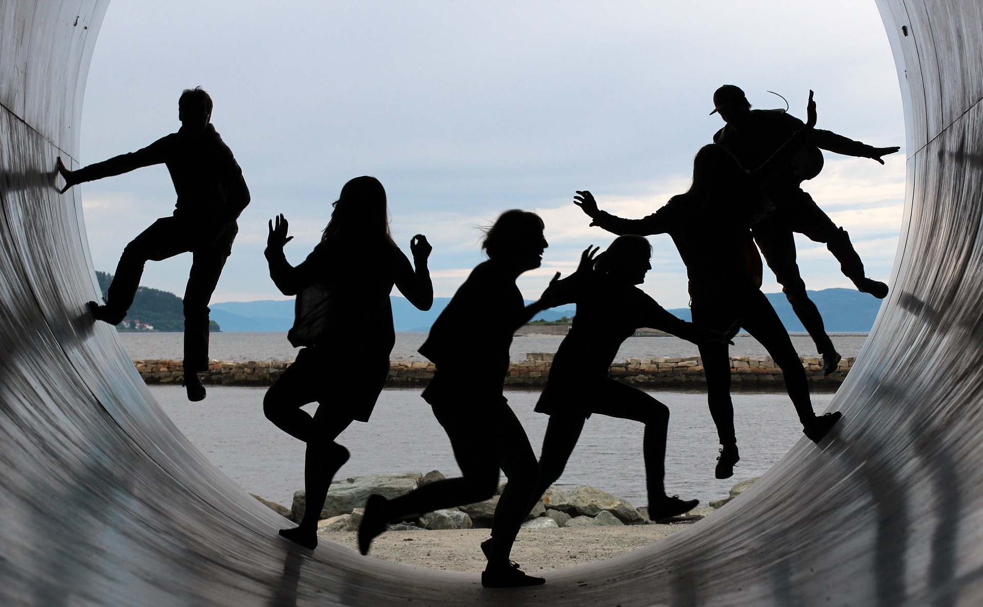 A shadowy group of individuals jump and play in a very large circular tube.