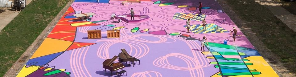 Image of a large outdoor area pinted with various shapes in pinks and purples with pianos and benches all over.