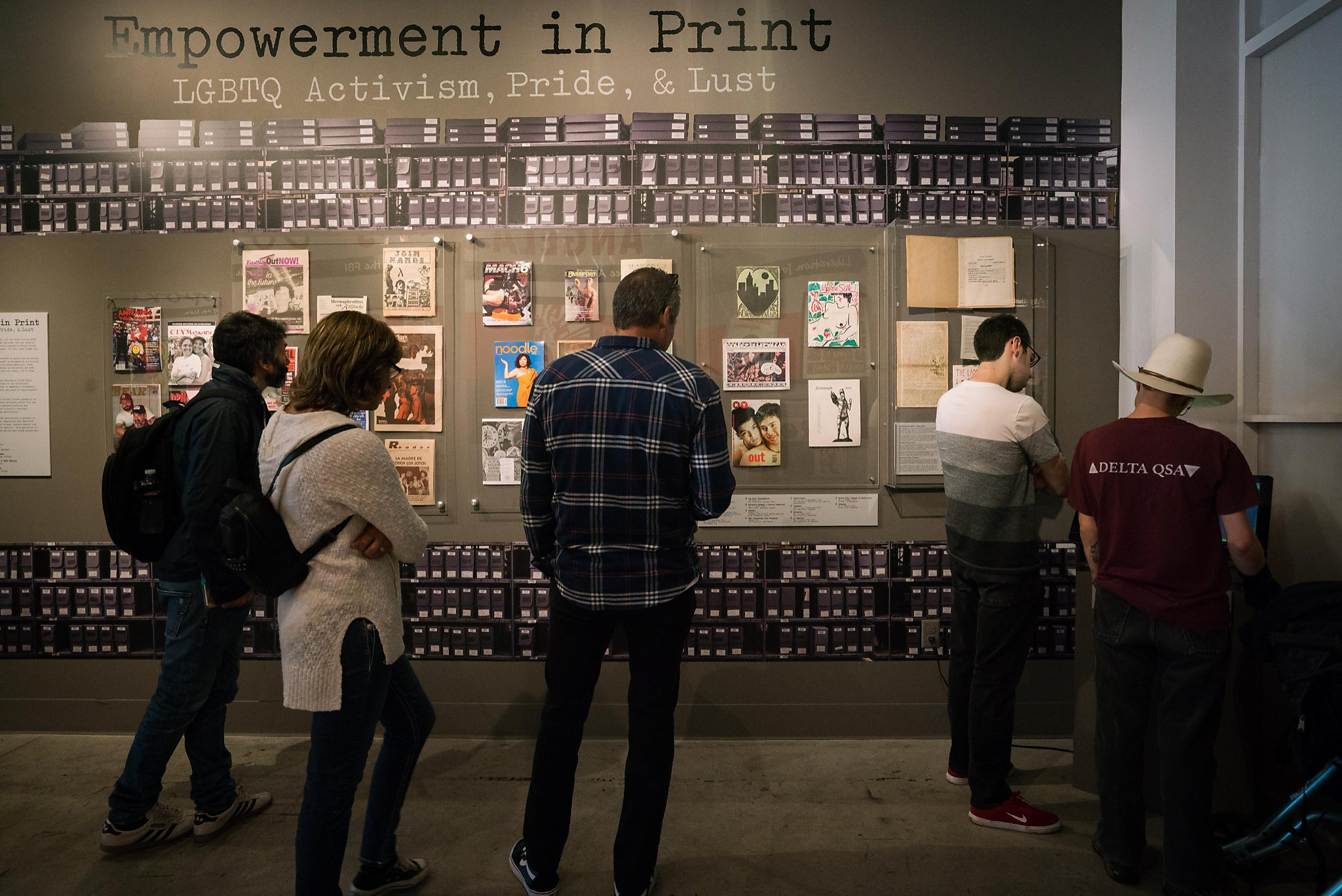 A group of people look at a display shown on a grey wall with a cityscape running along the top edge of the exhibit wall.