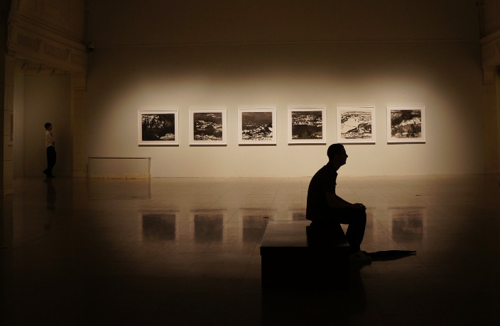 A sepia-toned image of a man sitting in a gallery contemplating a work of art. The wall behind him is backlit with a series of photographs.