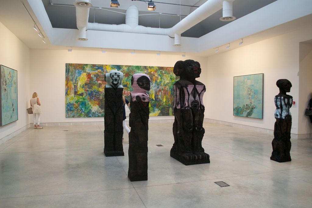 A gallery room with large scale paintings on the wall and 3 large sculptures in the center of the gallery floor.
