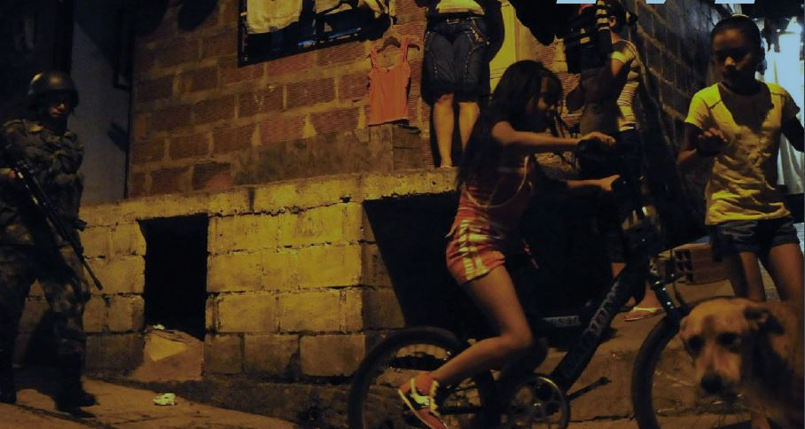 Two young girls ride their bicycles on a sidewalk next to a cinderblock house with a uniformed man with a large rifle behind them.