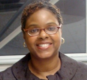 Headshot of a black woman with short red highlighted hair wearing red horn rimmed glasses smiling straight at the camera.