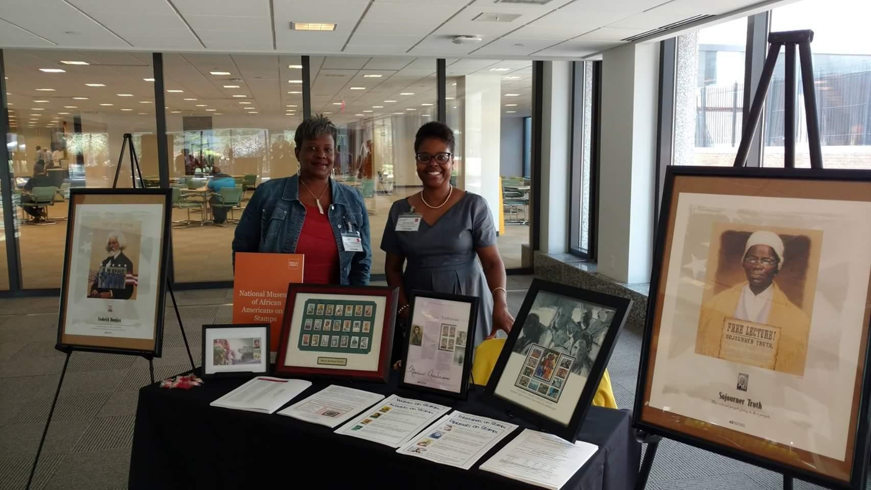 Two black women stand behind a table with various framed stamp collections.