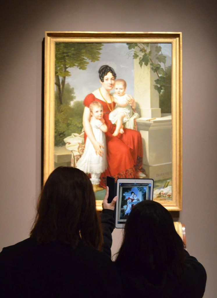 Two teens face a framed painting of a mother with two children on her lap. The two teens hold up a cell phone that is displaying the painting with additional text.