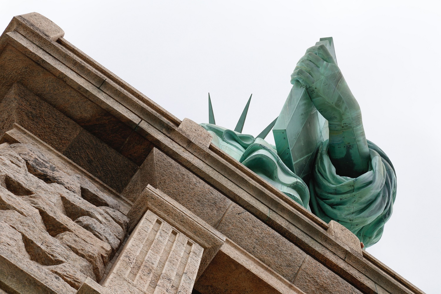 View of the Statue of Liberty taken from below at an angle so that all that is visible is her hand with the book in it an da few spikes from her crown an dthe edge of the plinth on which she stands.