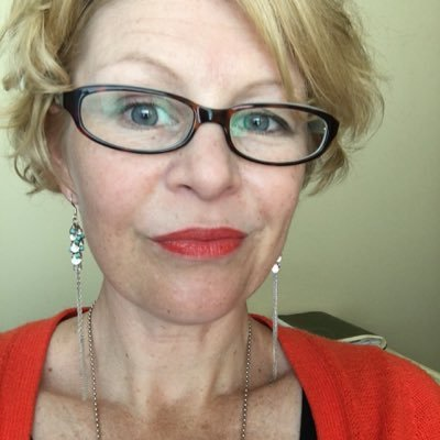 Selfie of a white woman with short blond hair and dark rimmed glasses looking quizzical at the camera.
