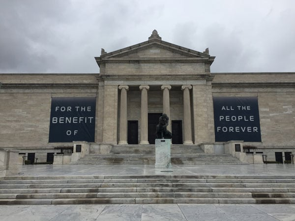 Exterior shot of the facade of the Cleveland Museum of Art, a classical style building with a colunmed portico and wide staircase leading to it.