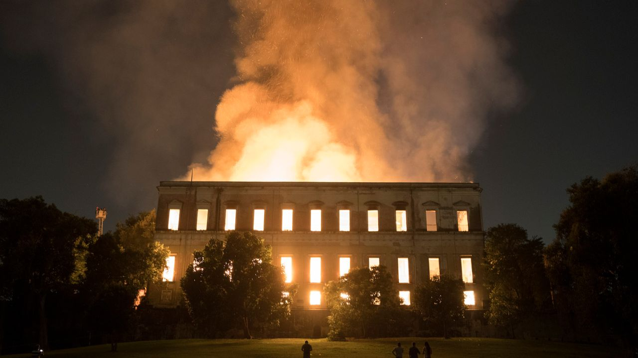 Exterior image of the National Museum of Brazil taken from the side showing flames erupting from the roof and the windows all show glowing fire within.