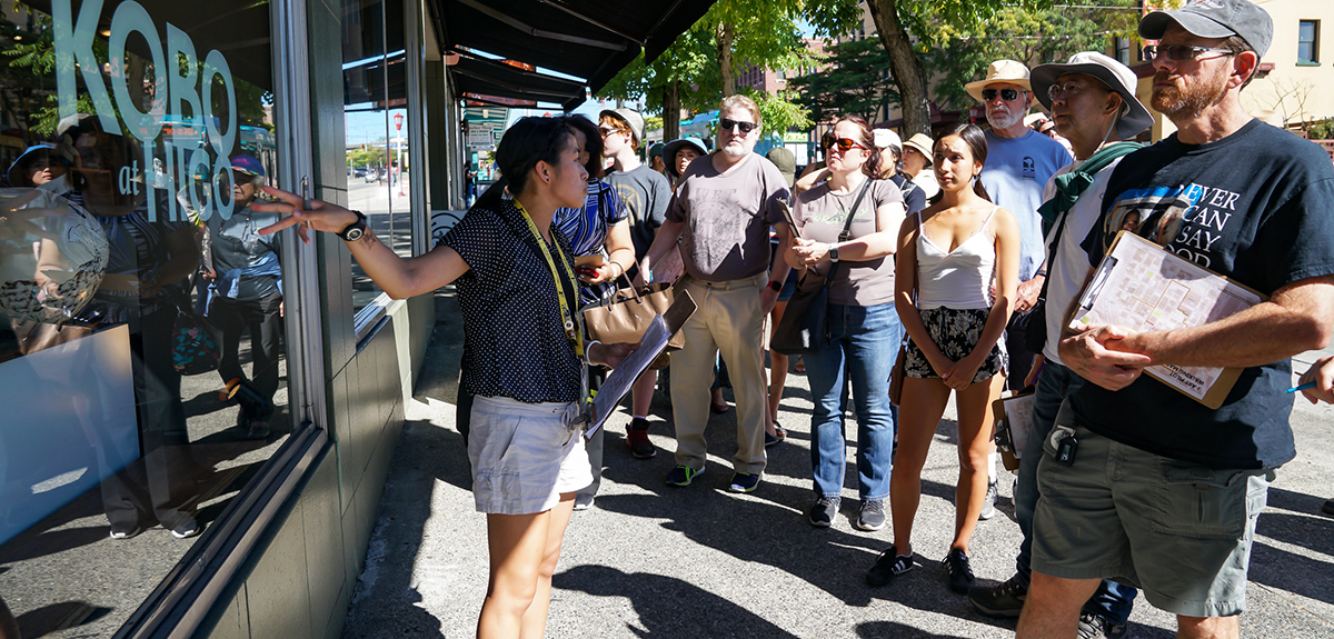 A tour guide discusses one business at a storefront with a diverse group of individuals.