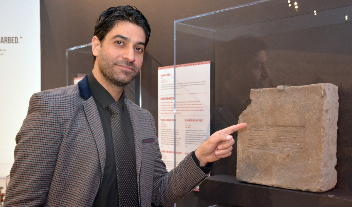 A Middle Eastern man points at an object in a case hanging on a wall behind a plaxiglas vitrine.