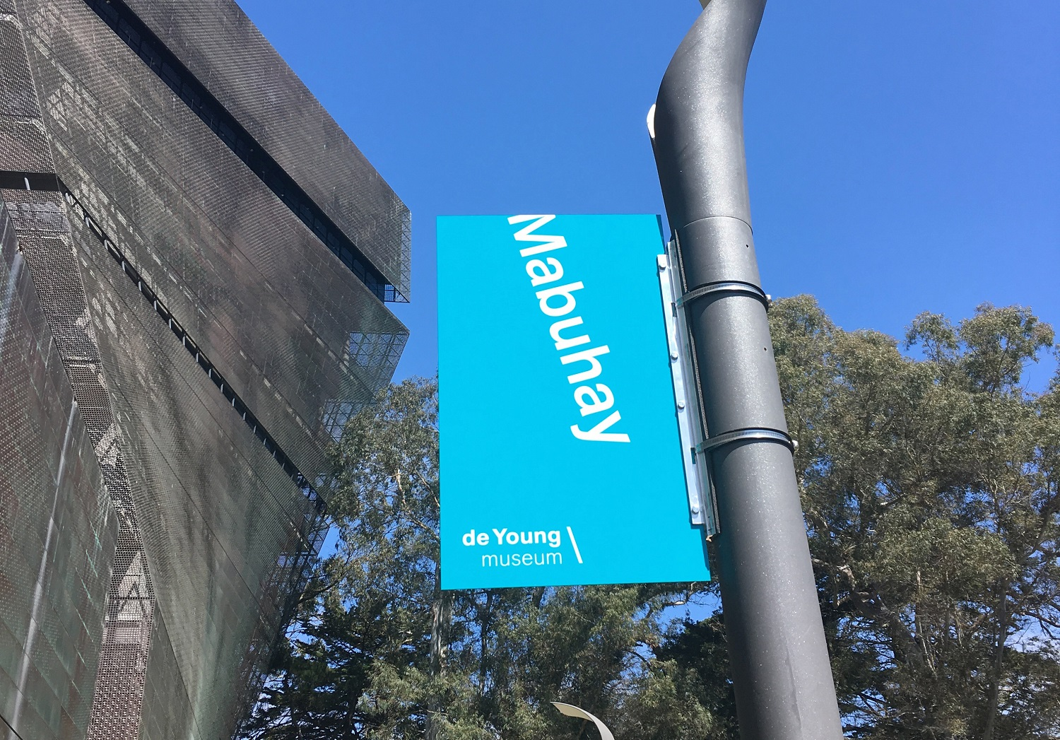 Exterior image of the de Young museum with a Mabuhay/Welcome banner in teal with white letters hanging from a lamp post.